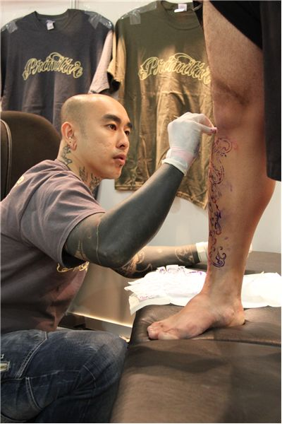 Picture Of Tattoo Artist Drawing A Design